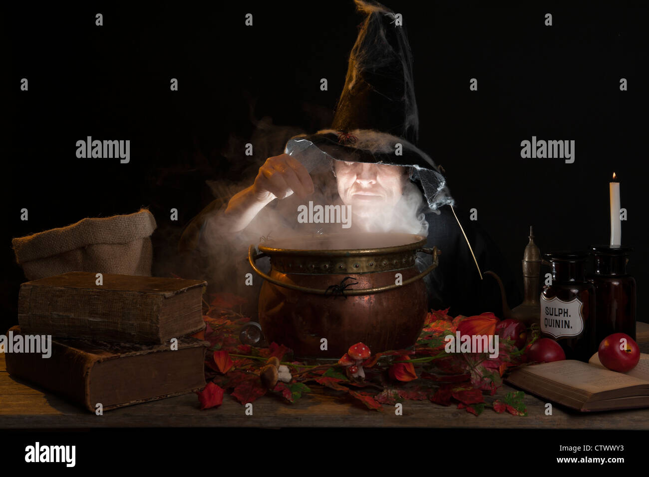 halloween making a potion in a copper cauldron - Stock Image