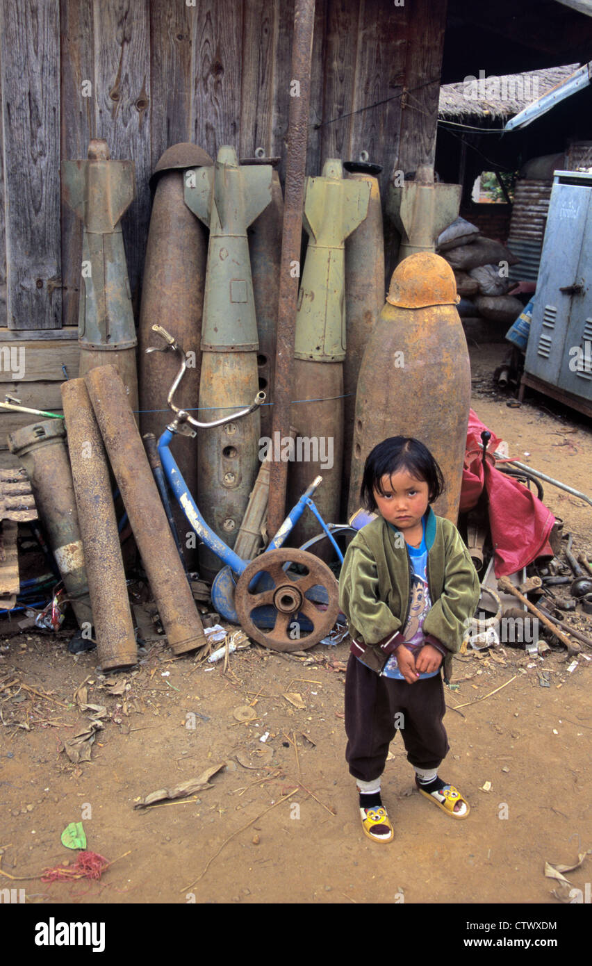 Young Lao or Laotian Girl in Scrap Metal Yard with War Waste Bombs and Missiles from the Vietnam War Phonsavan Laos - Stock Image