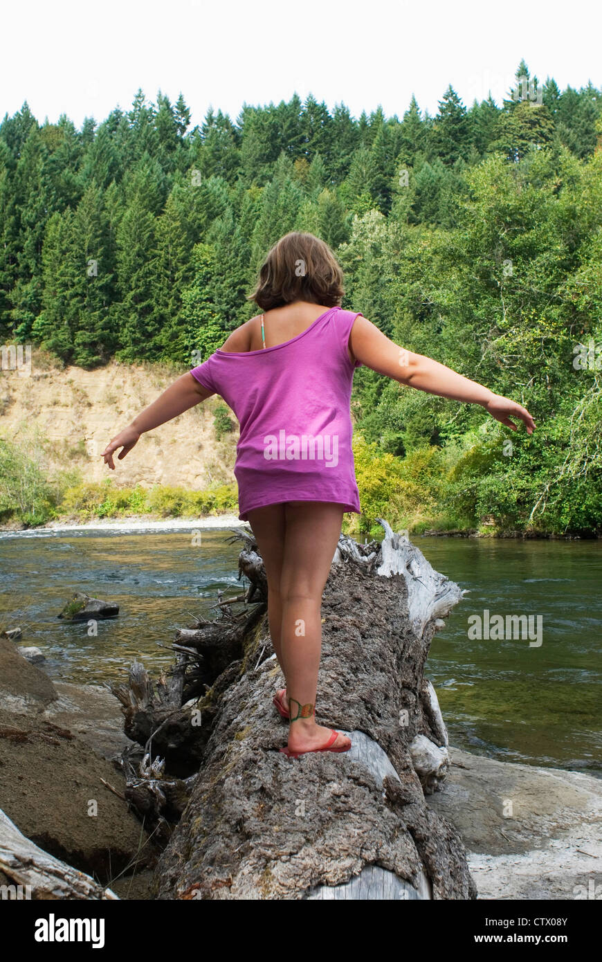 A young girl balancing on fallen tree trunk. - Stock Image