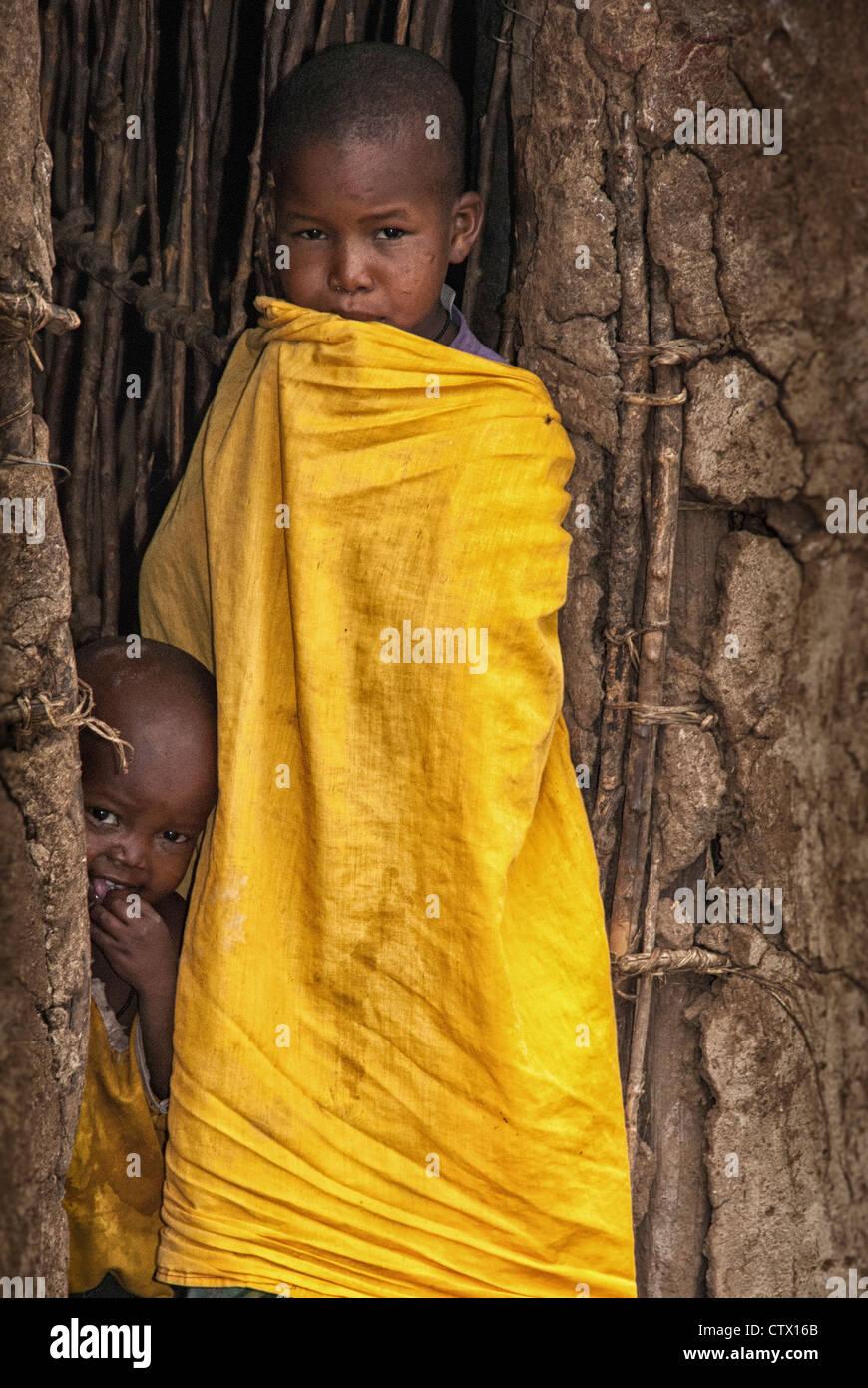 Masai Child in the doorway of a mud hut in a village near the Masai Mara, Kenya, East Africa Stock Photo