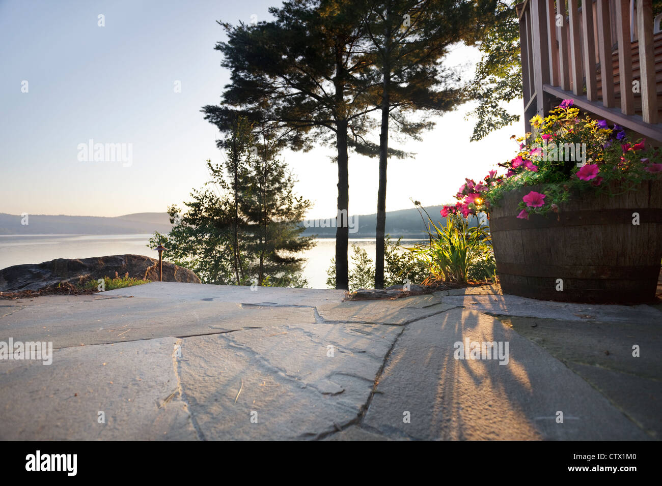 Early morning sun spills onto a lakeside patio and flower barrel Stock Photo