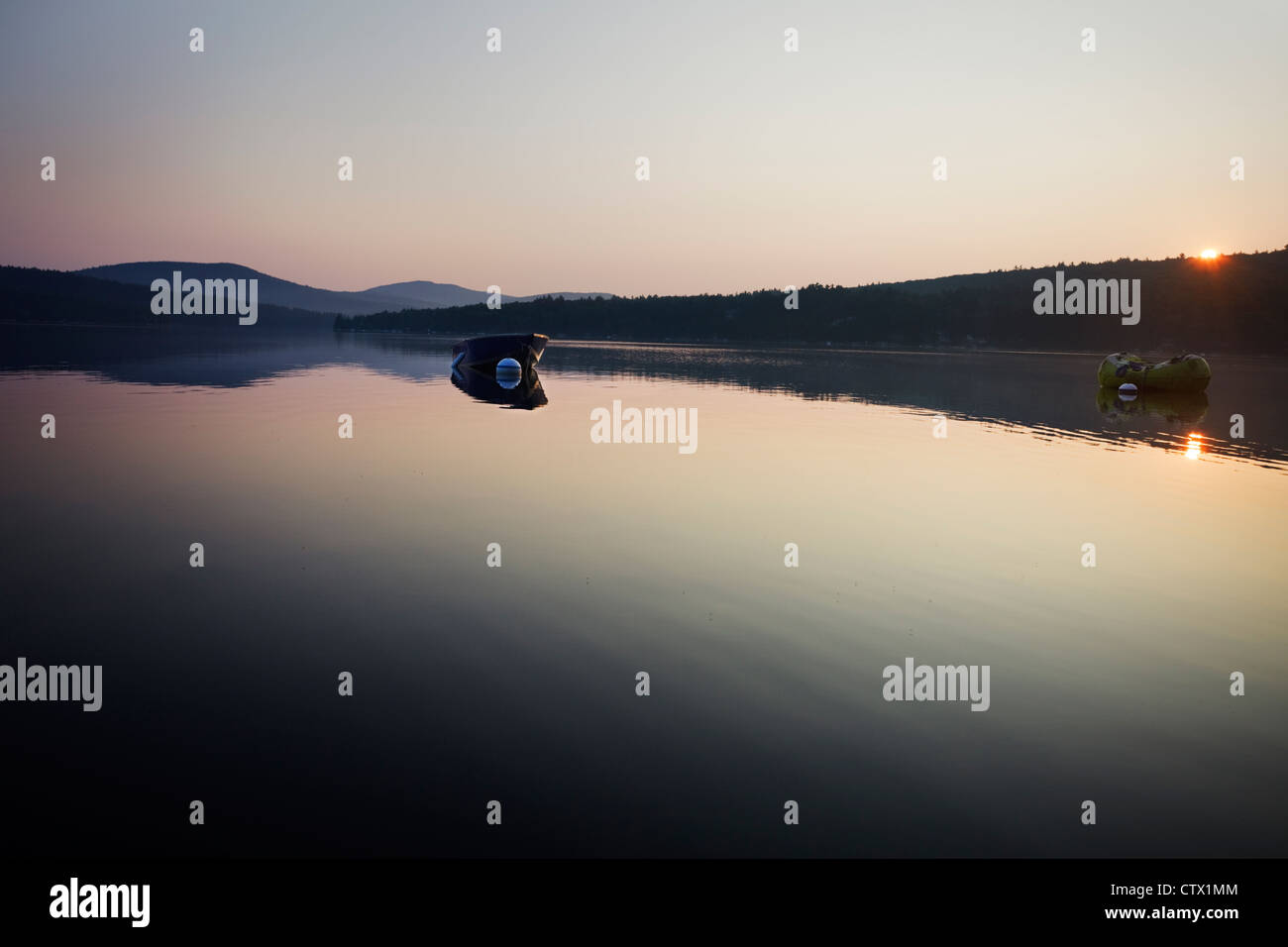Sun rises over the hills on a calm Summer morning at the lake - Stock Image