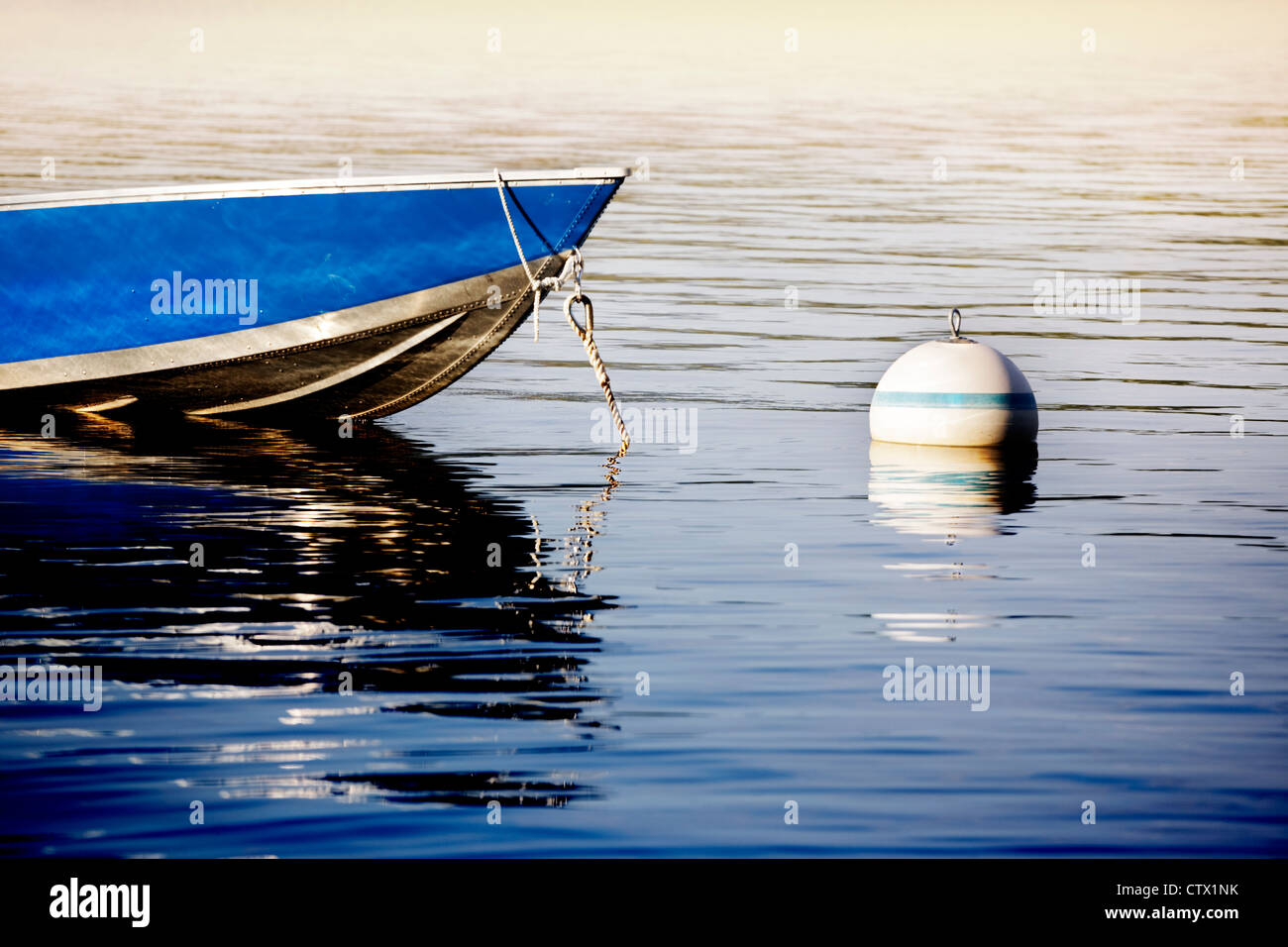 Small dinghy tied up to a buoy on a lake as the sun goes down - Stock Image