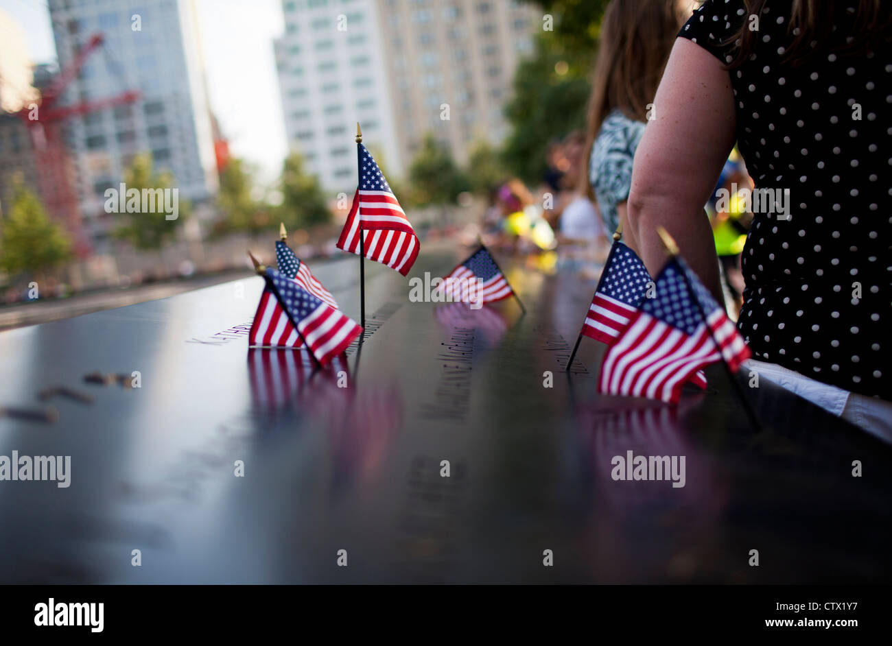 American flags are placed in some of the names of the 2,983 victims at the 9-11 Memorial in New York City. - Stock Image