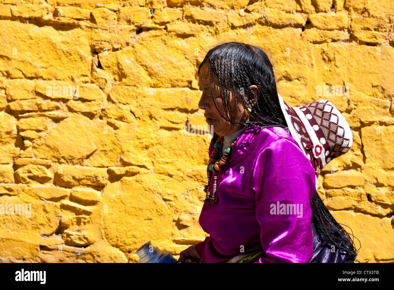 A Tibetan woman wearing traditional clothes is passing a yellow wall, Tibet, - Stock Image