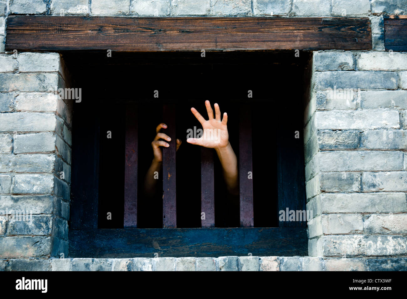 Prisoner hands stretch out from prison bars - Stock Image