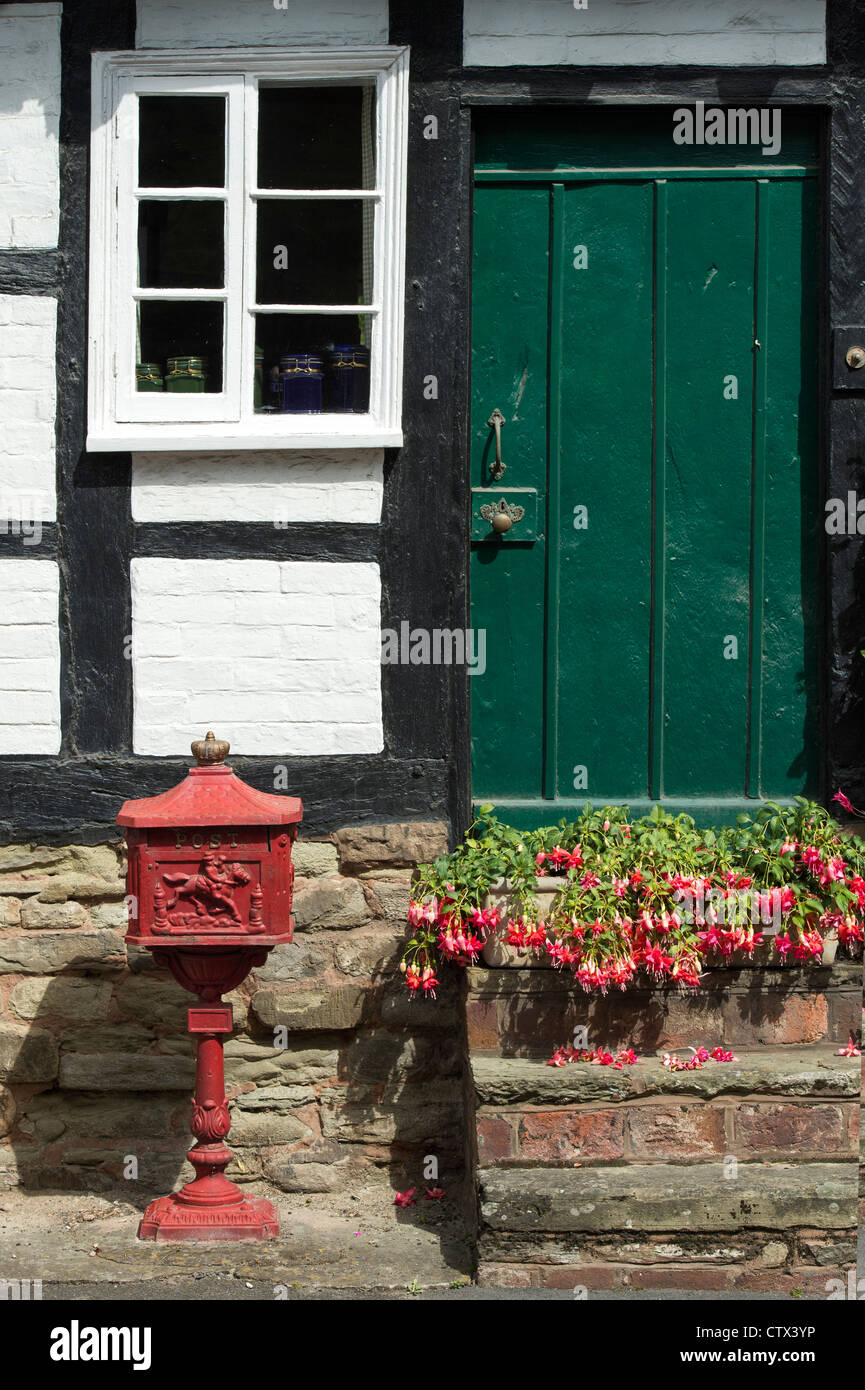 Old historic royal mail post box outside a Black and White English Timber framed building. Pembridge. Herefordshire. - Stock Image