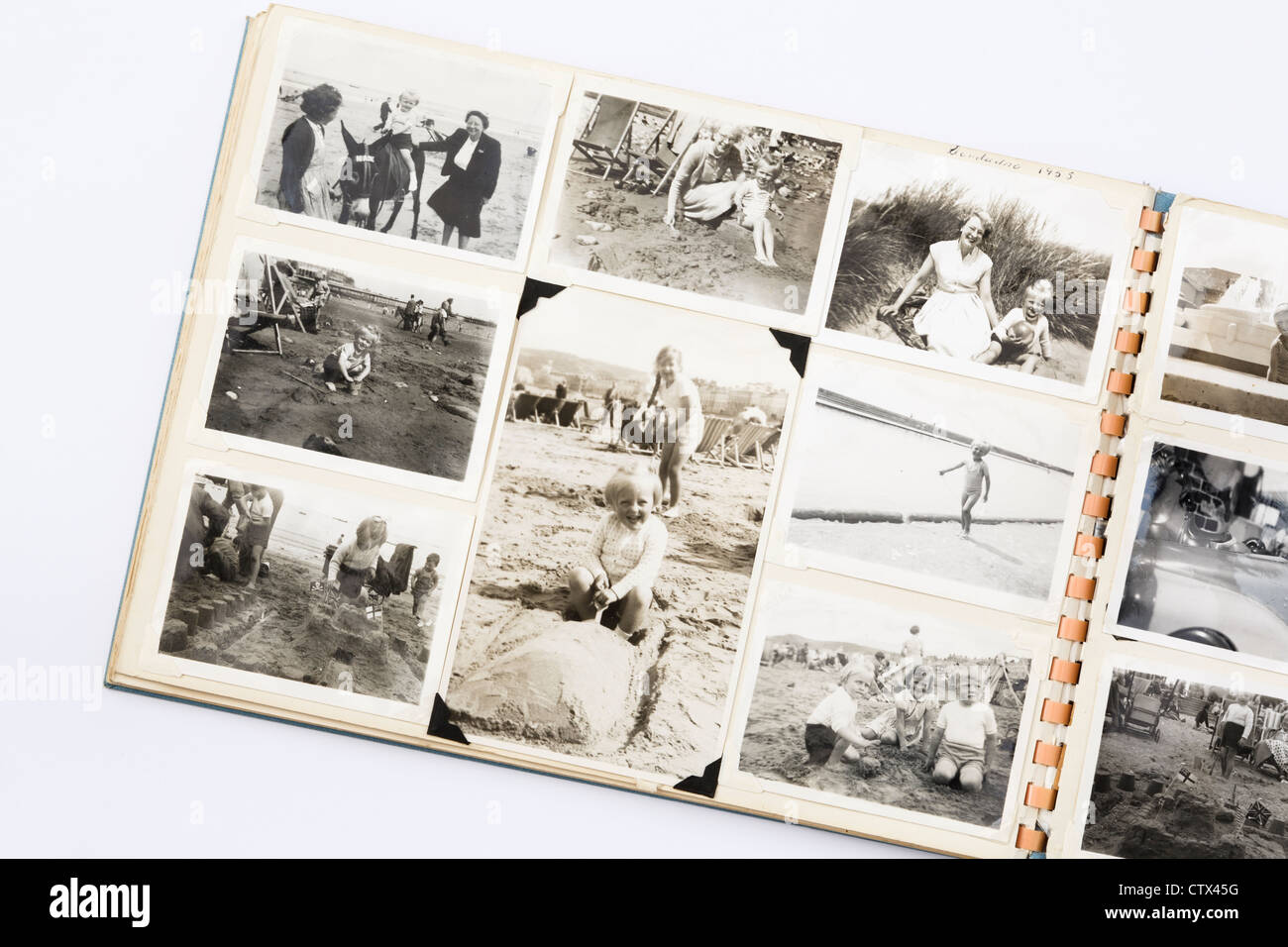 Old faded black and white printed photographs in a family photograph photo album from 1950s era with page showing - Stock Image