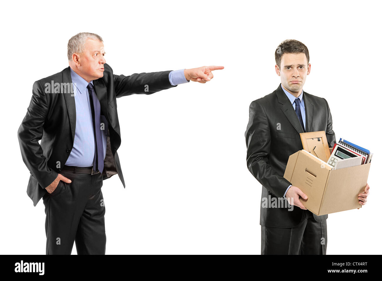 An angry boss firing a man carrying a box of personal items isolated on white background - Stock Image