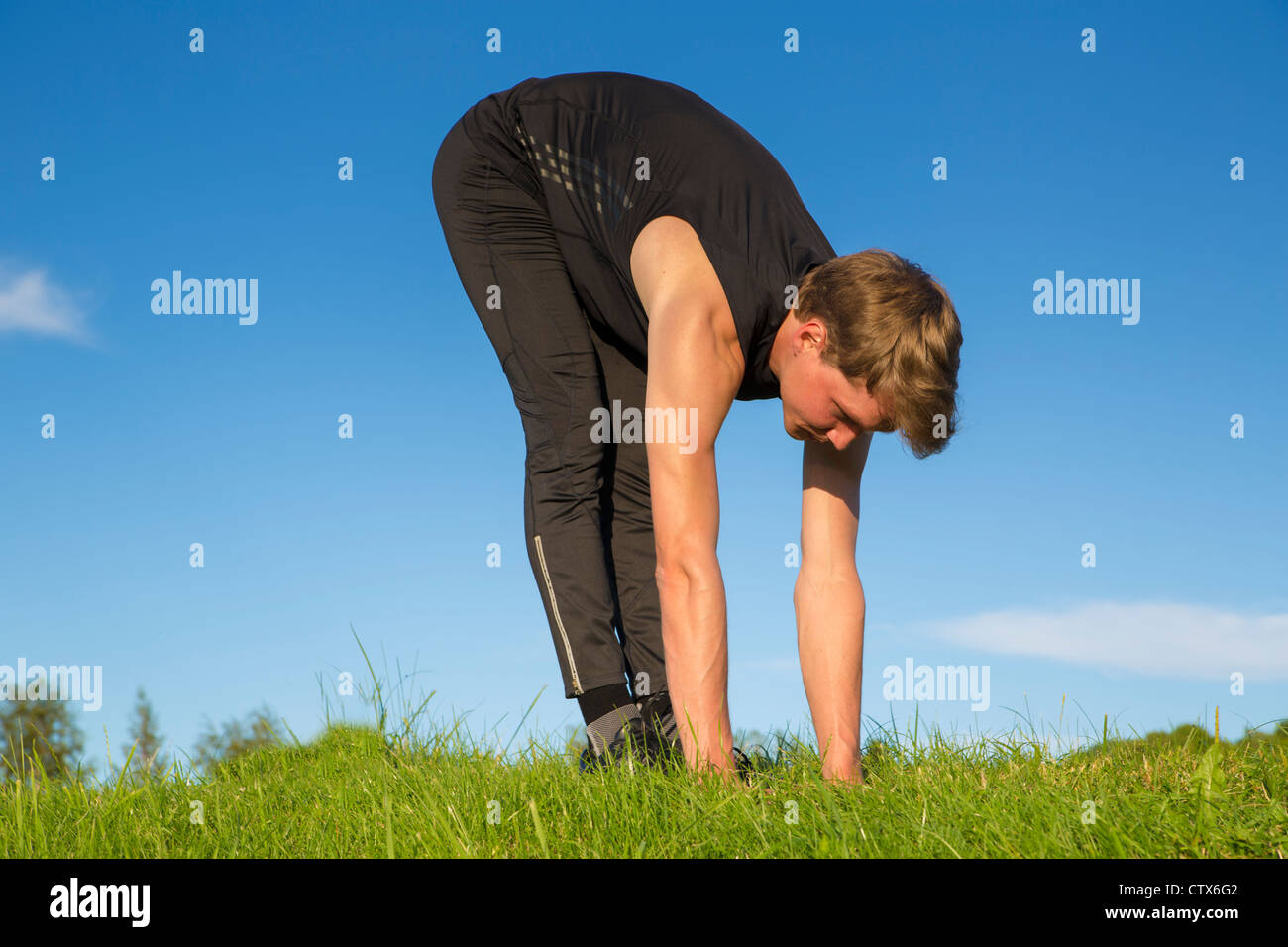 Sportsman making exercise movements to stretch its muscles - Stock Image