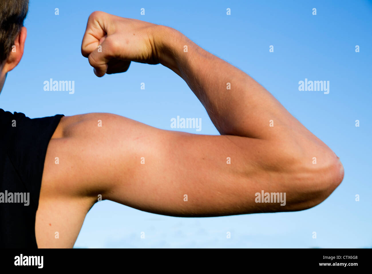 Sportsman show its muscles when strain strong hand - Stock Image