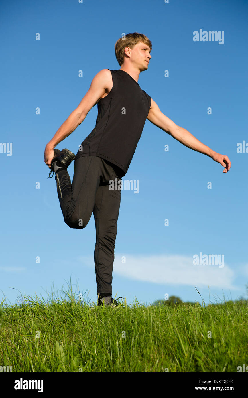 Sportsman is stretch right leg crook on behind - Stock Image
