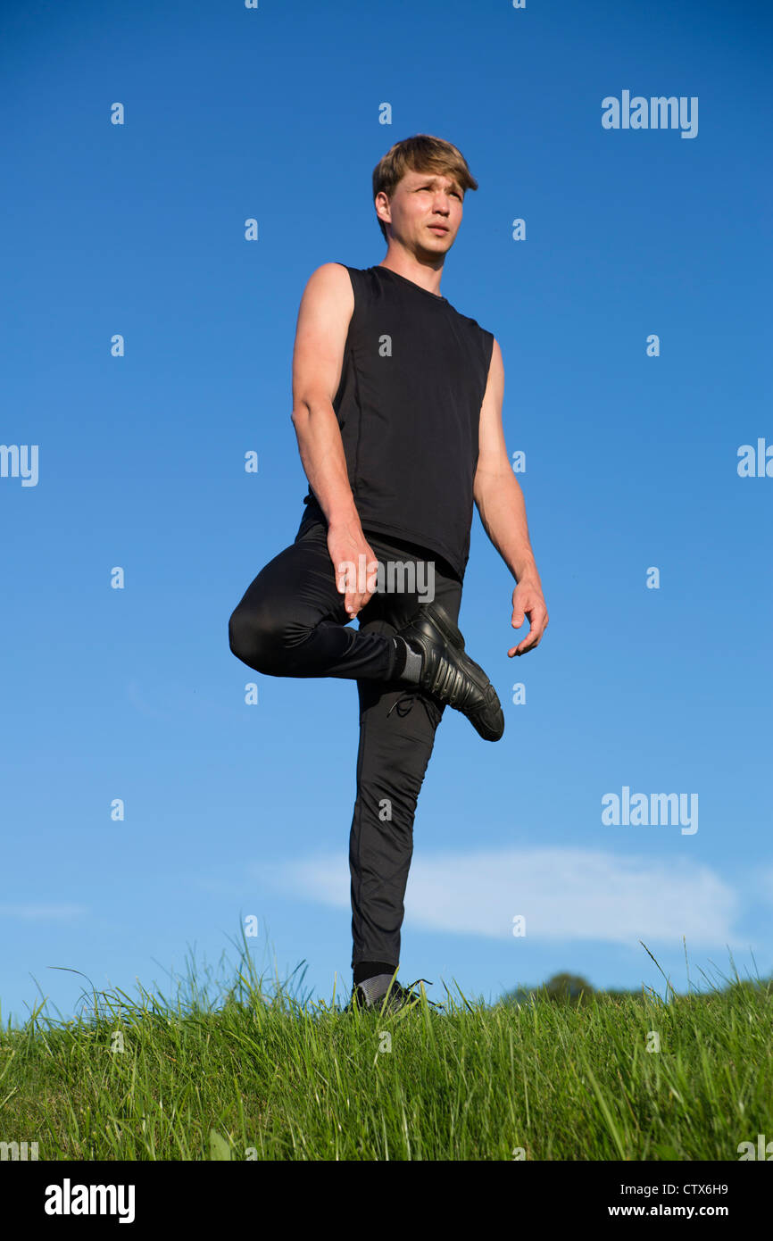 Sportsman is stretch right leg crook on before - Stock Image