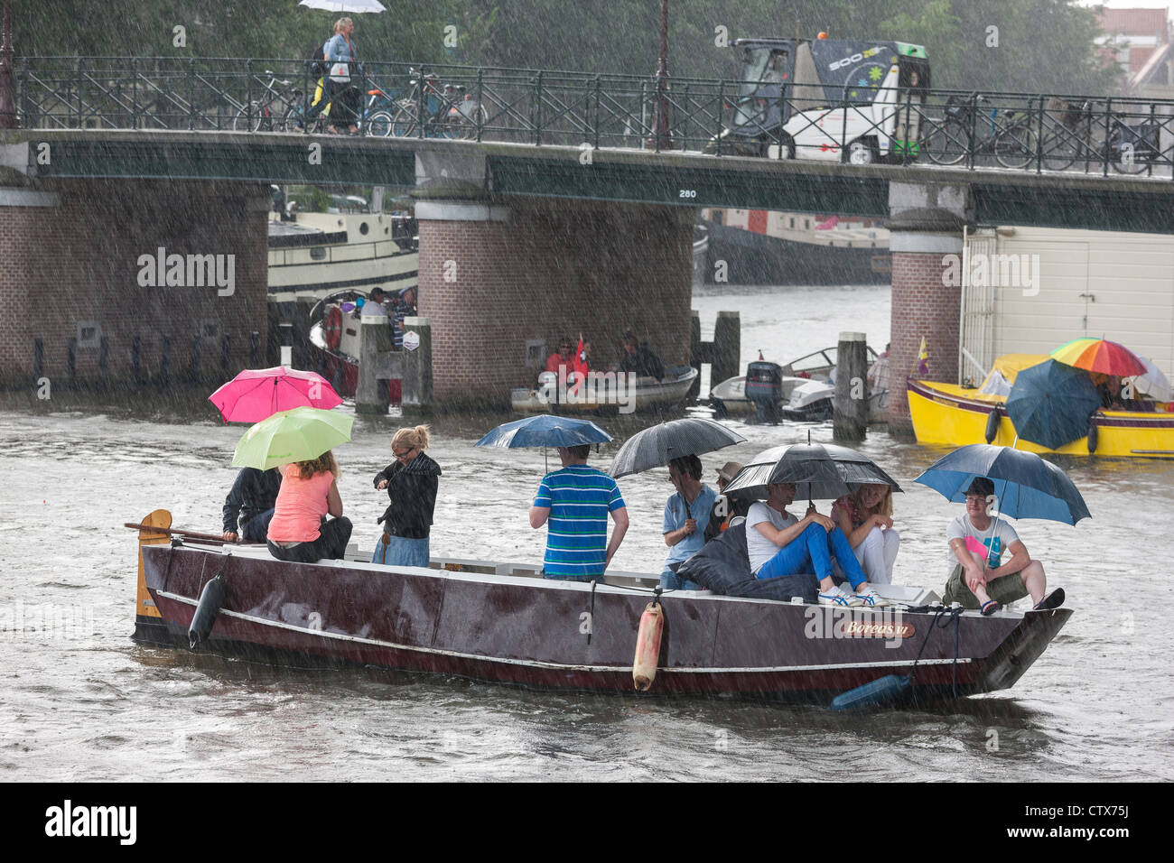 Sudden torrential summer rain in Amsterdam. 9 people in a small boat, sloop, with umbrellas. - Stock Image