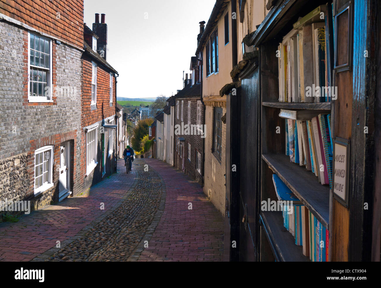 View down historic cobbled Keere Street with bookshop in foreground Lewes Sussex UK Stock Photo