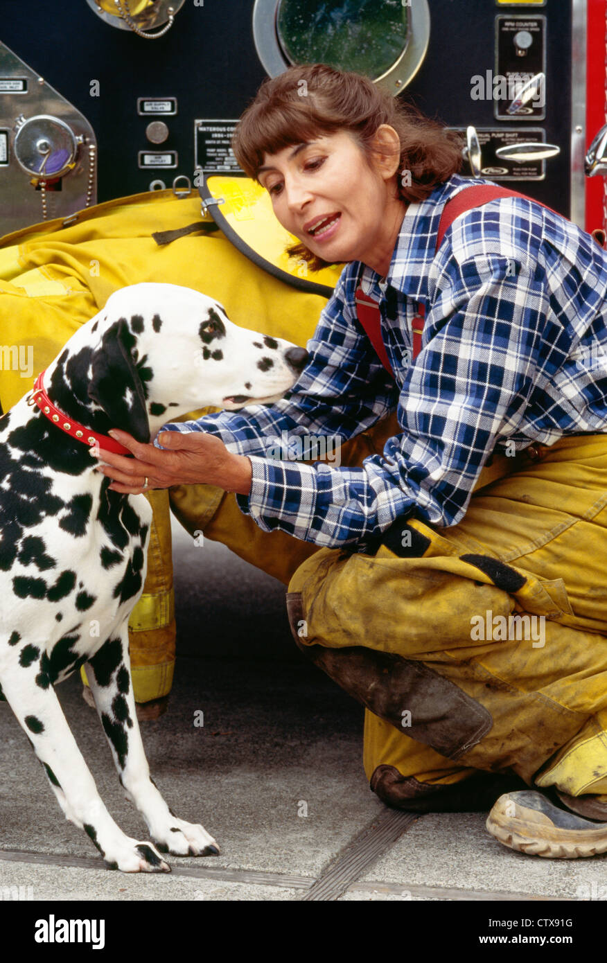 Female Firefighter And Dalmatian At Firehouse