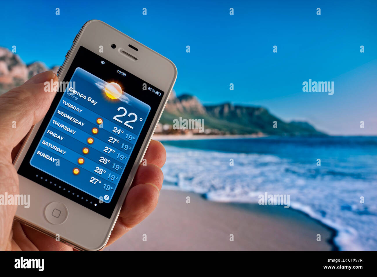Hand holding white Apple iPhone 4s displaying 22C morning sun on weather forecast application at Camps Bay Capetown - Stock Image