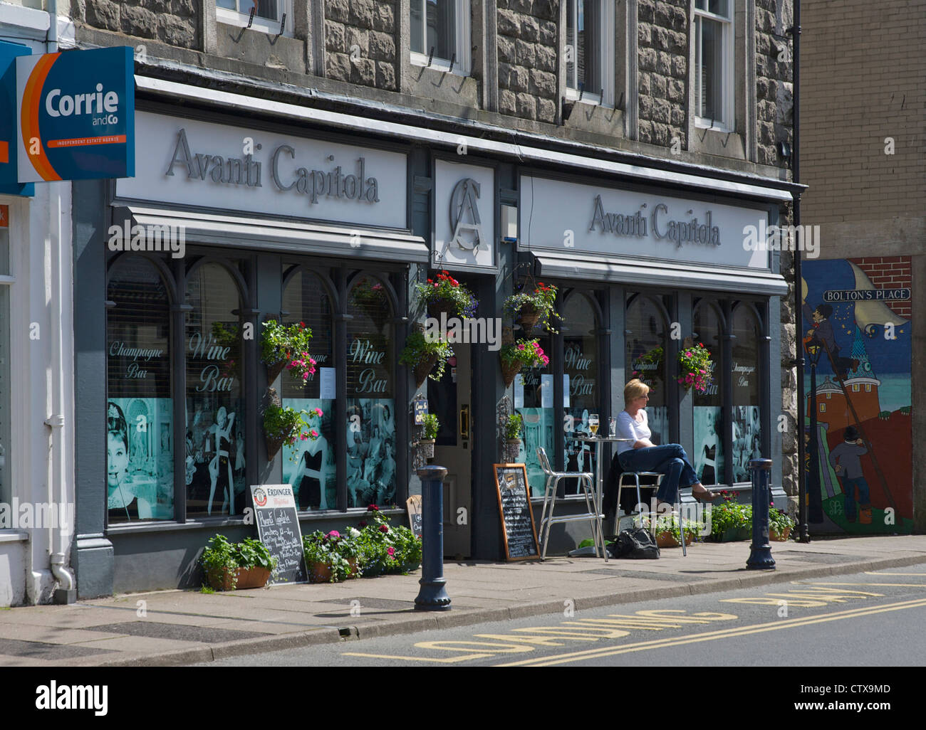 Middle-aged woman sitting outside wine bar in the town of Ulverston, South Lakeland, Cumbria, England UK - Stock Image