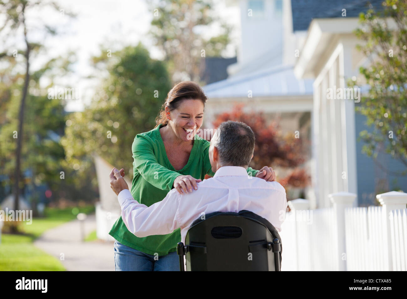 Couple happily greeting each other while he is in a wheelchair with a spinal cord injury - Stock Image