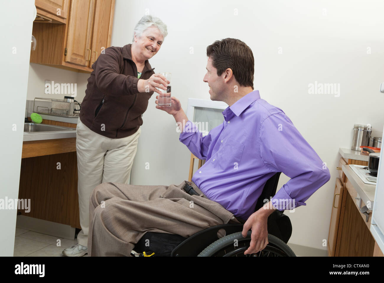 Home health aid offering a glass of water to a man in wheelchair with spinal cord injury - Stock Image