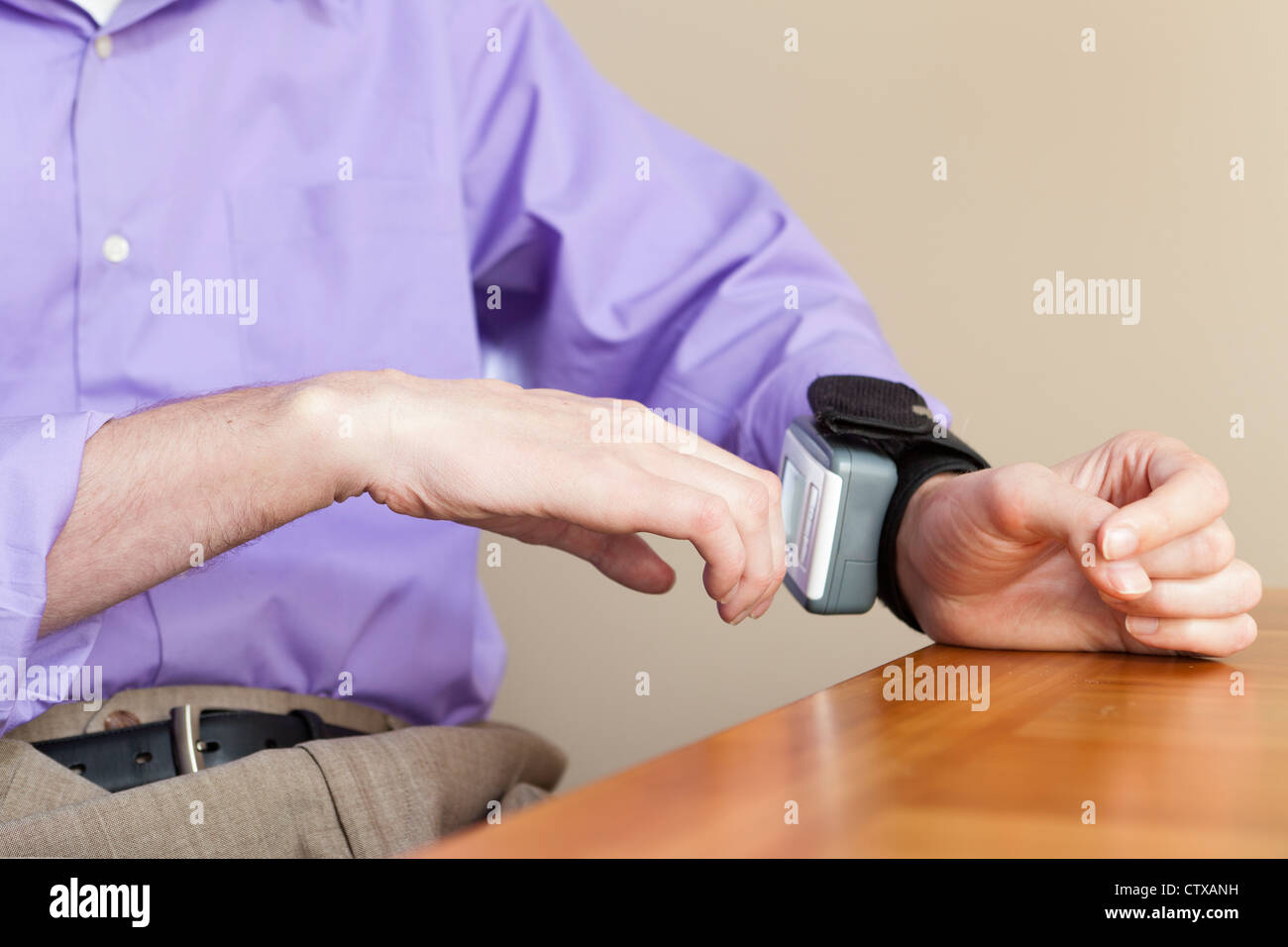 Man with spinal cord injury checking his blood pressure gauge on his wrist - Stock Image