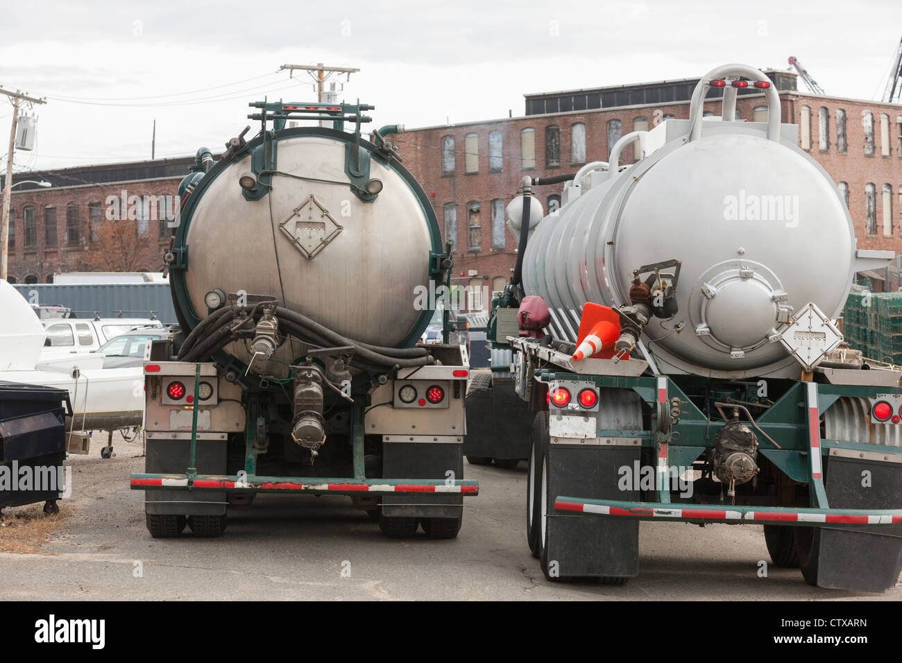 Two hazardous waste tanker trucks for picking up petroleum from ships in harbor - Stock Image
