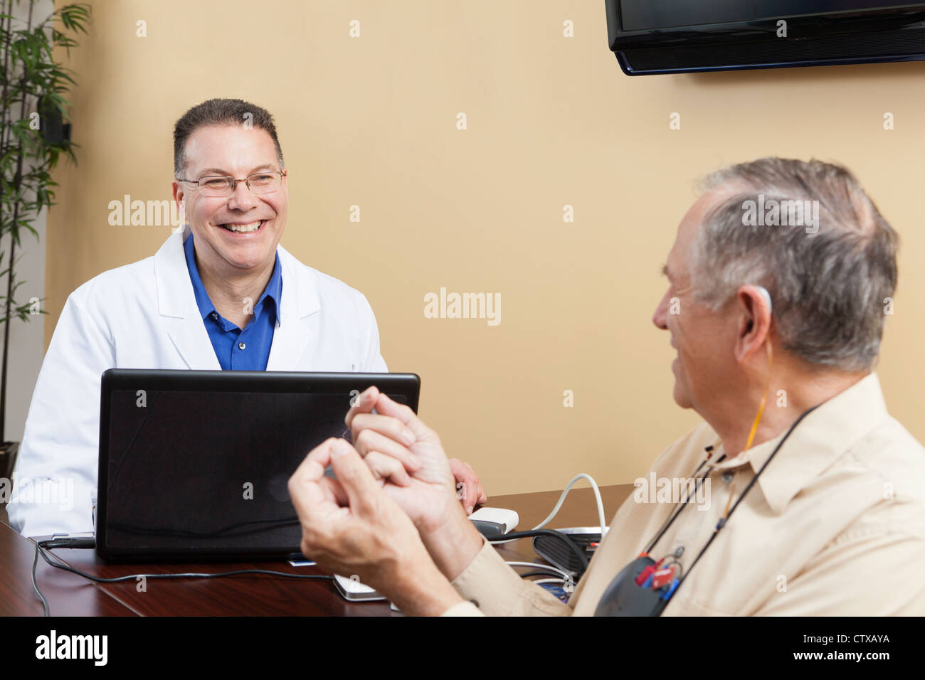 Patient providing feedback to an audiologist for hearing aid programming - Stock Image