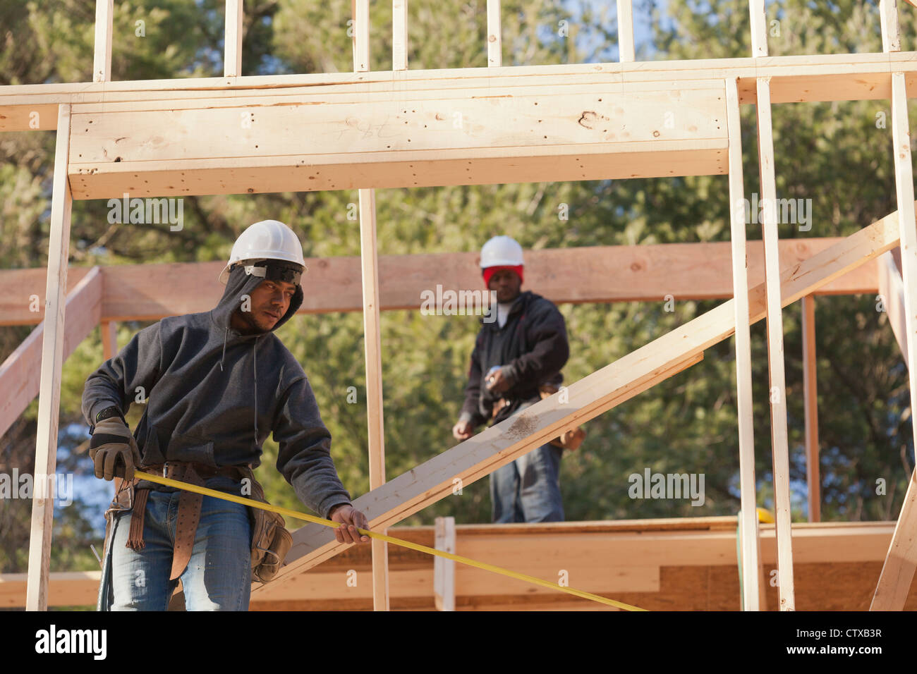 Carpenter measuring width of picture window frame - Stock Image