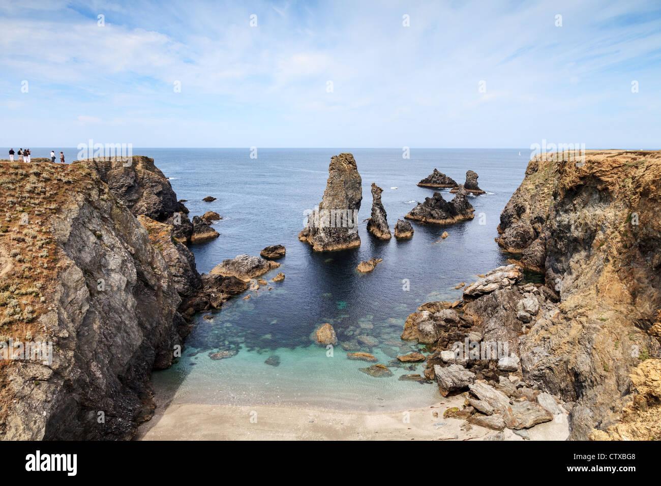 Tourist party on the cliff above Les Aiguilles de Port Coton, Belle-Ile, Brittany, France. - Stock Image