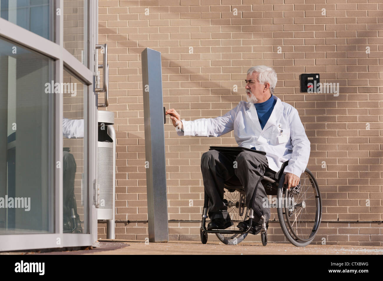 Doctor with muscular dystrophy in wheelchair at hospital entrance pressing knob for accessible door & Doctor with muscular dystrophy in wheelchair at hospital entrance ...