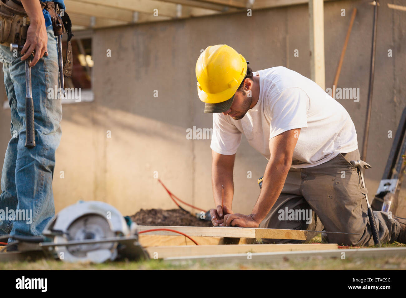 Carpenter measuring deck joist for cutting - Stock Image