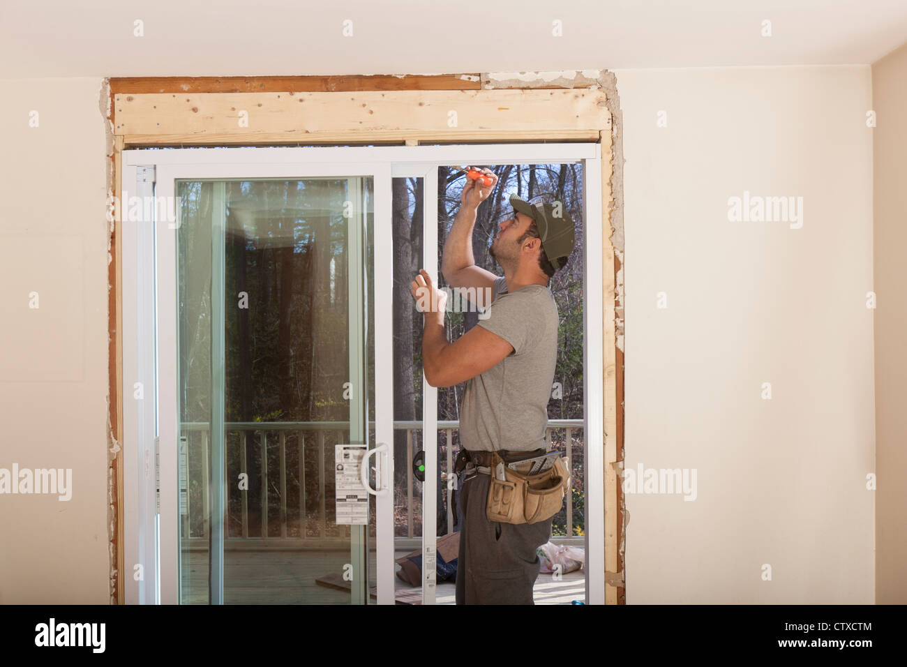Hispanic carpenter installing glass doors in new door frame for deck access on house : installing doors - pezcame.com