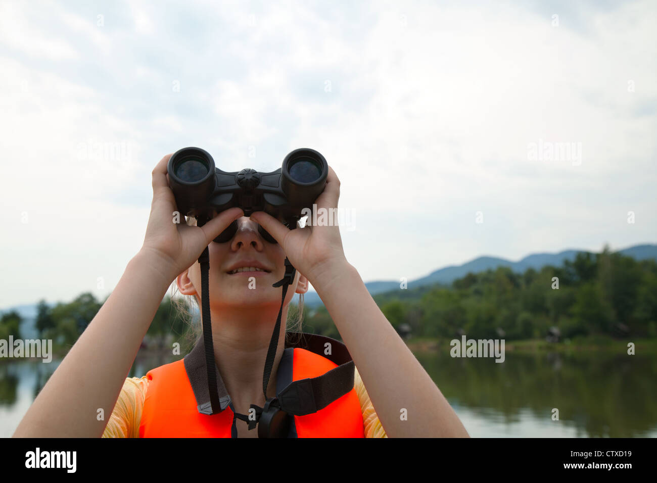 Young woman looking to sky through binoculars - Stock Image
