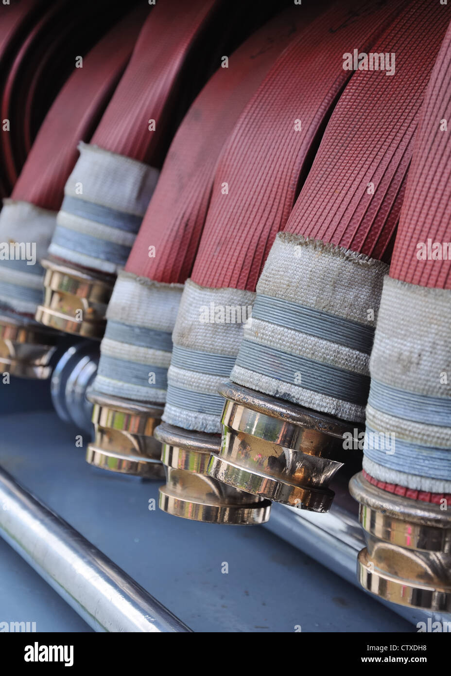 Close up of shiny brass couplings on fire service hose. - Stock Image
