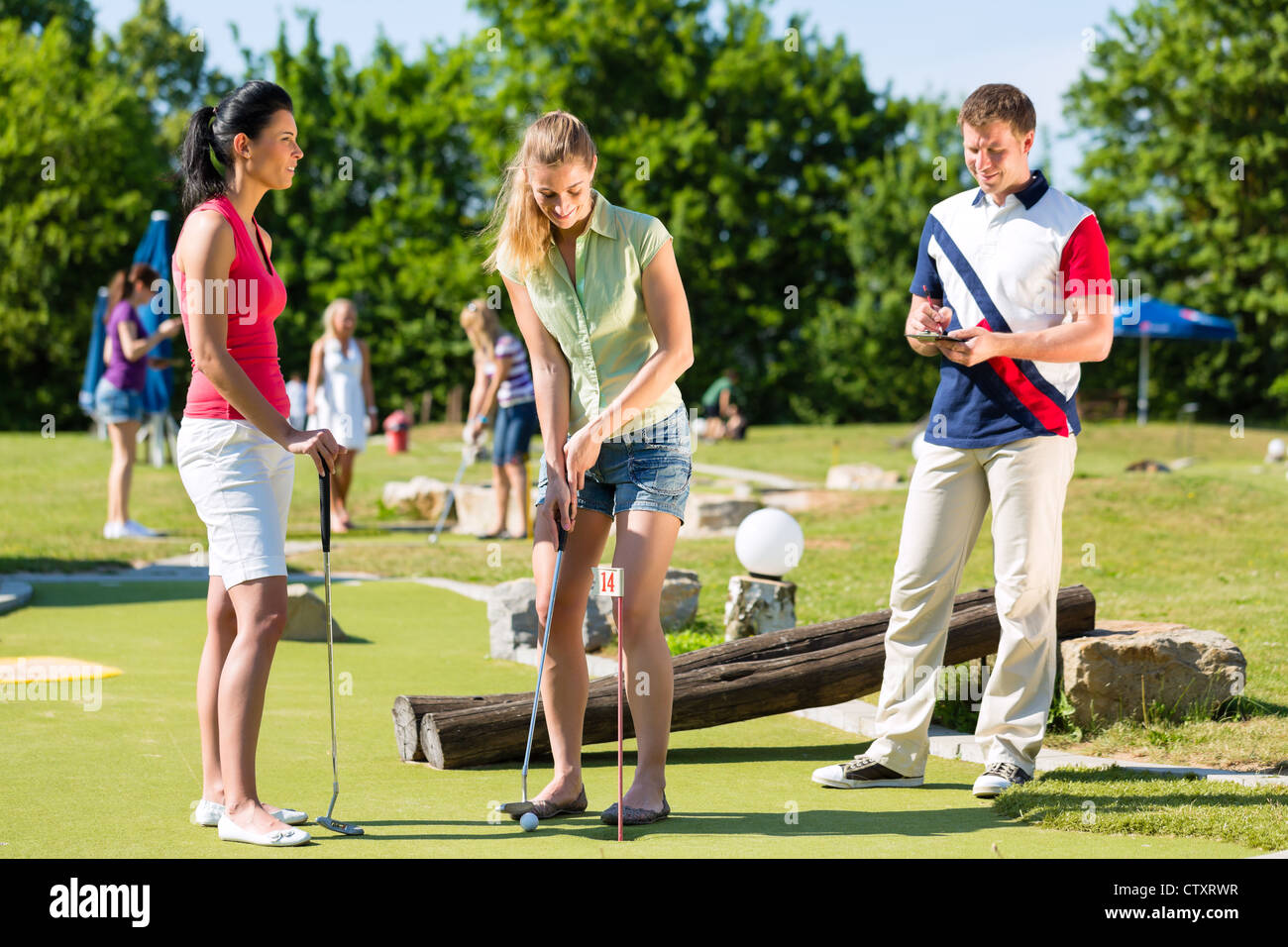 People, man and women, playing miniature golf on a beautiful summer day Stock Photo