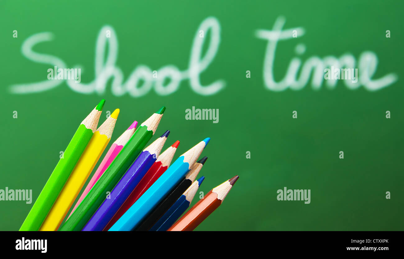 Back to school concept, green chalkboard with handwriting and set of colorful drawing pencils - Stock Image