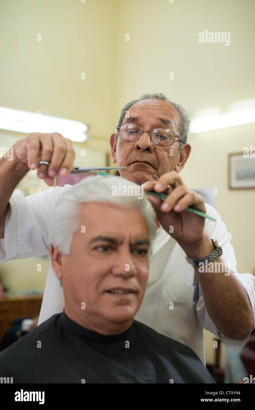 Active retired old people, man getting an haircut by senior barber in old fashion barber's shop. Copy space - Stock Image