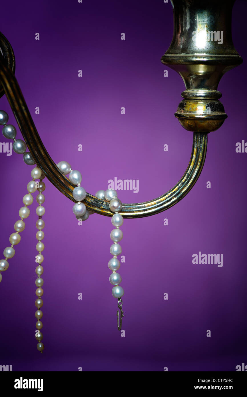 Pearl necklace on an old candle stick in front of a purple drape - Stock Image