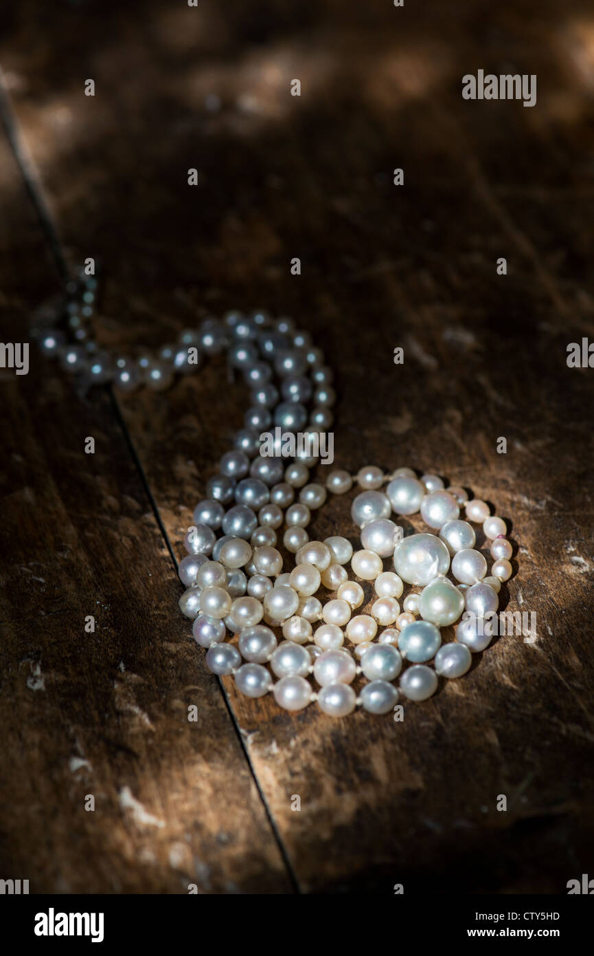 Pearl necklace on old oak floor boards in the sunlight - Stock Image
