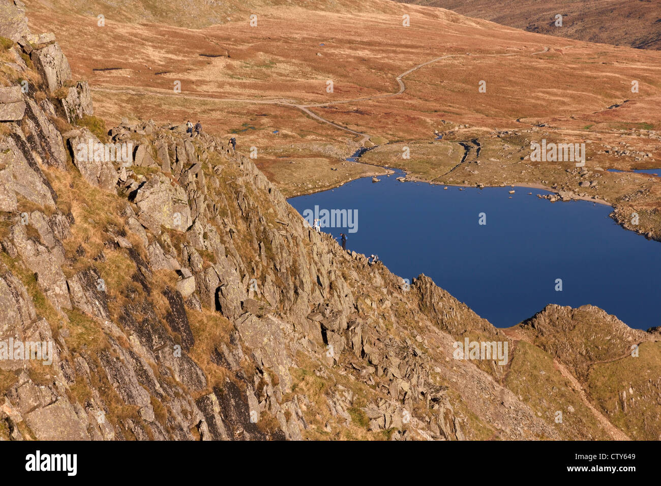 Hill walkers ascending Helvellyn from Striding Edge, Helvellyn, Lake District, Cumbria, England, UK - Stock Image