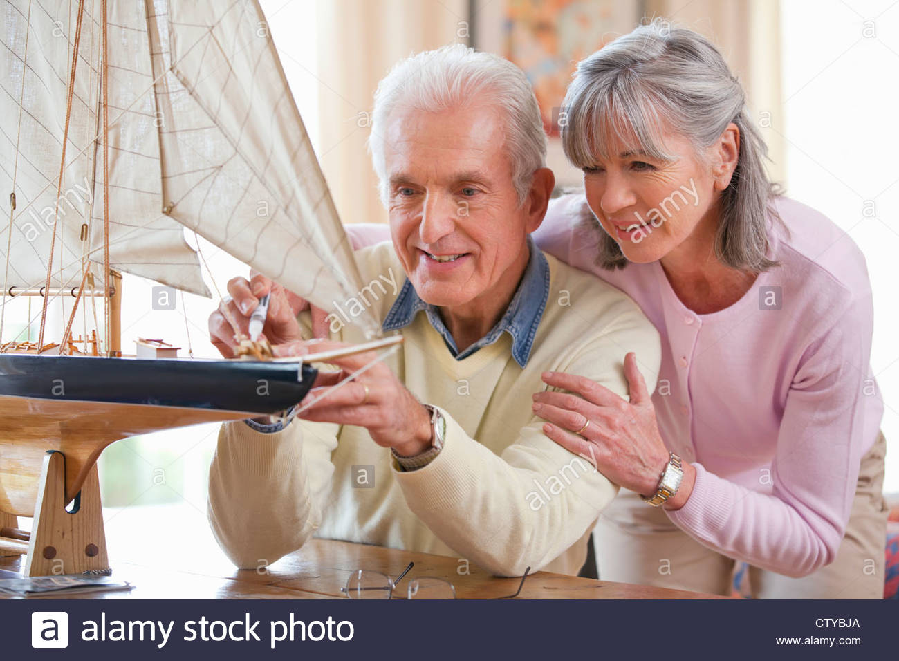 Senior woman watching senior man apply glue to model sailboat Stock Photo