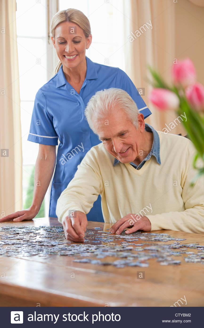 Home caregiver watching senior man assemble jigsaw puzzle on table - Stock Image