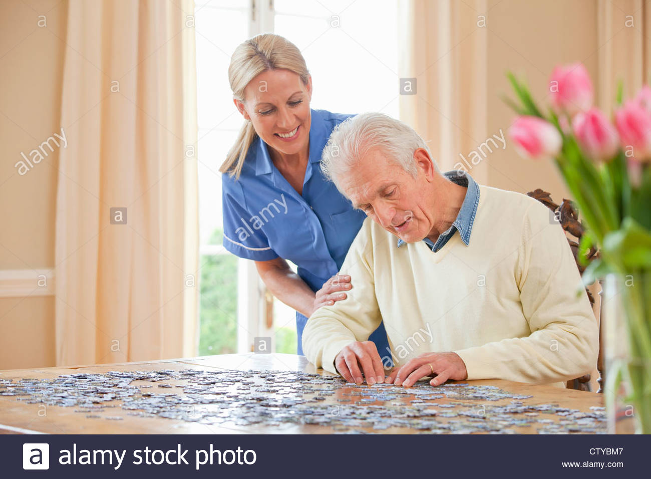 Smiling home caregiver watching senior man assemble jigsaw puzzle on table - Stock Image
