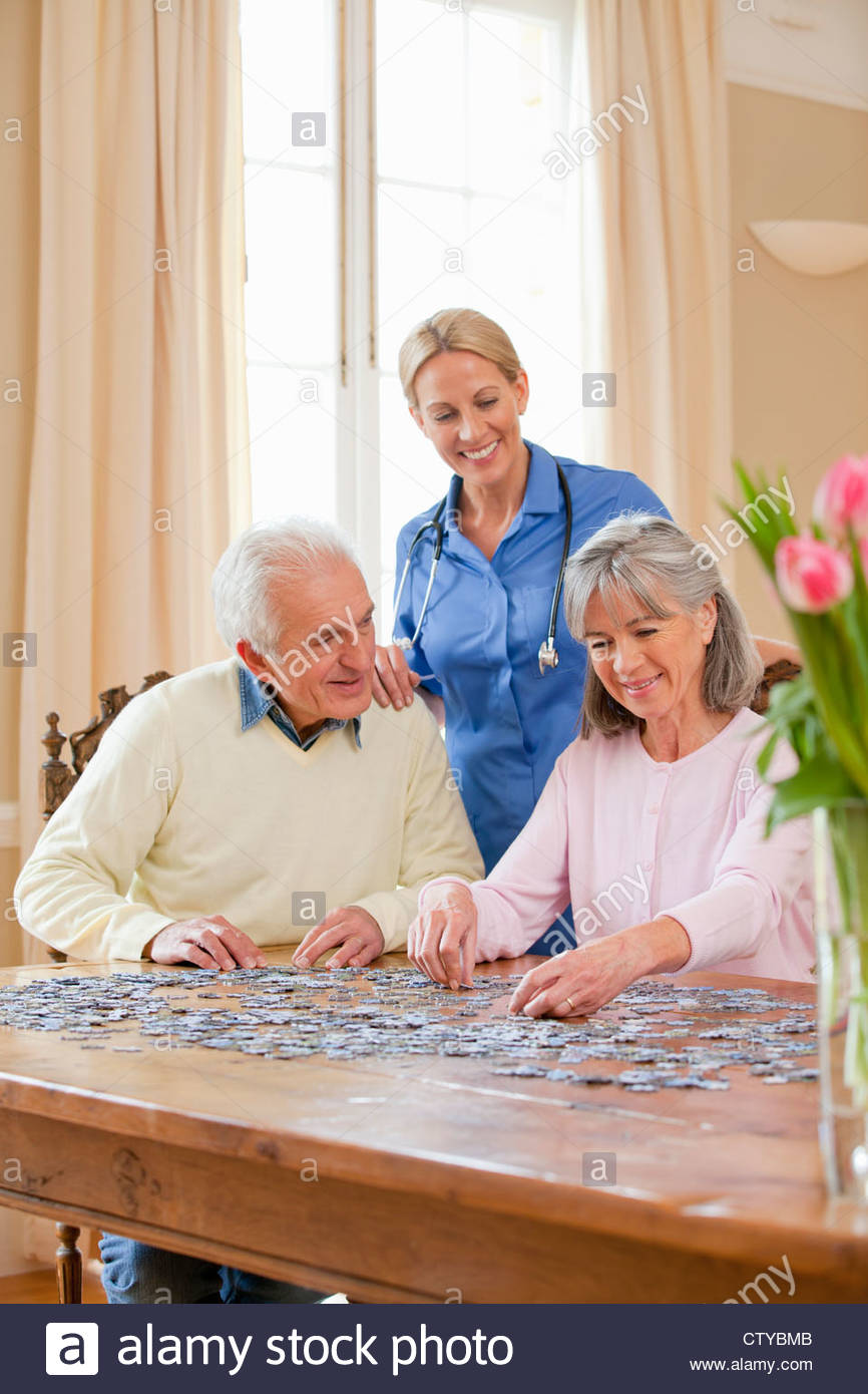 Smiling home caregiver watching senior senior couple assemble jigsaw puzzle on table - Stock Image