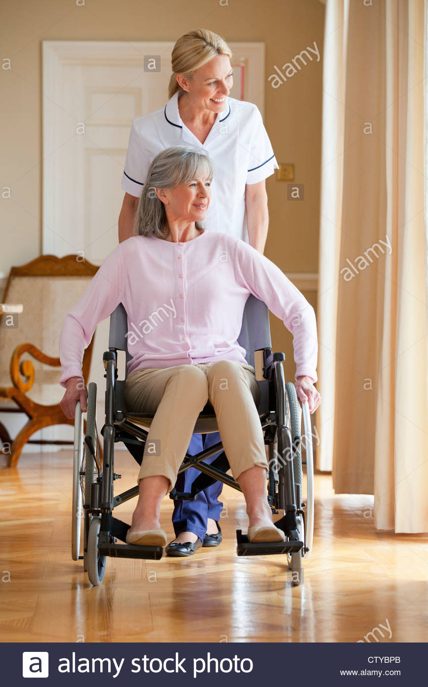 Smiling home caregiver pushing senior woman in wheelchair - Stock Image