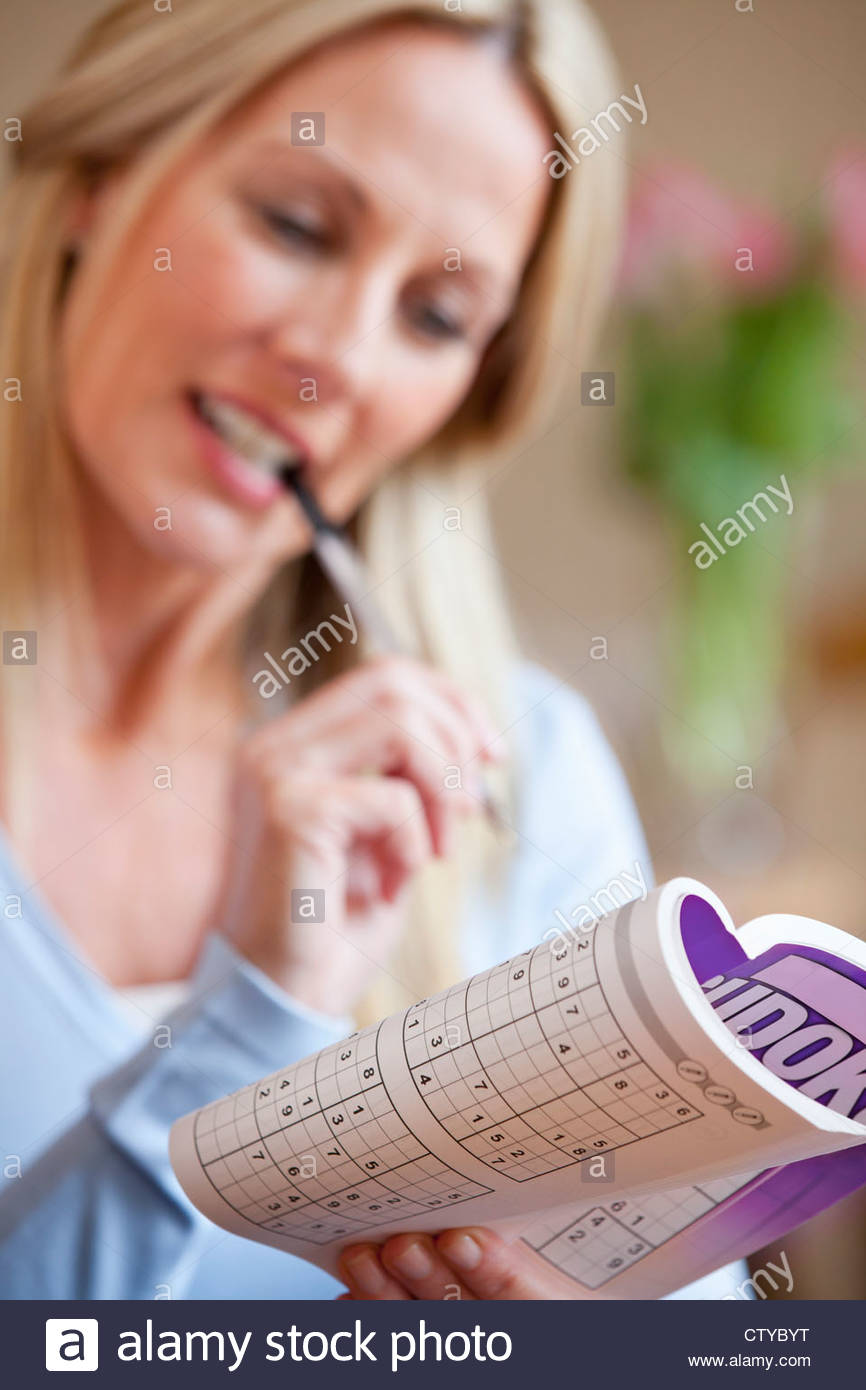 Close up of woman holding sudoku book - Stock Image