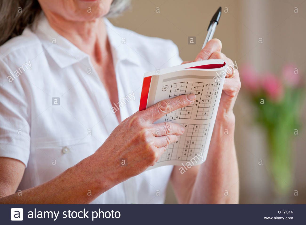 Close up of senior woman holding sudoku book and pen - Stock Image