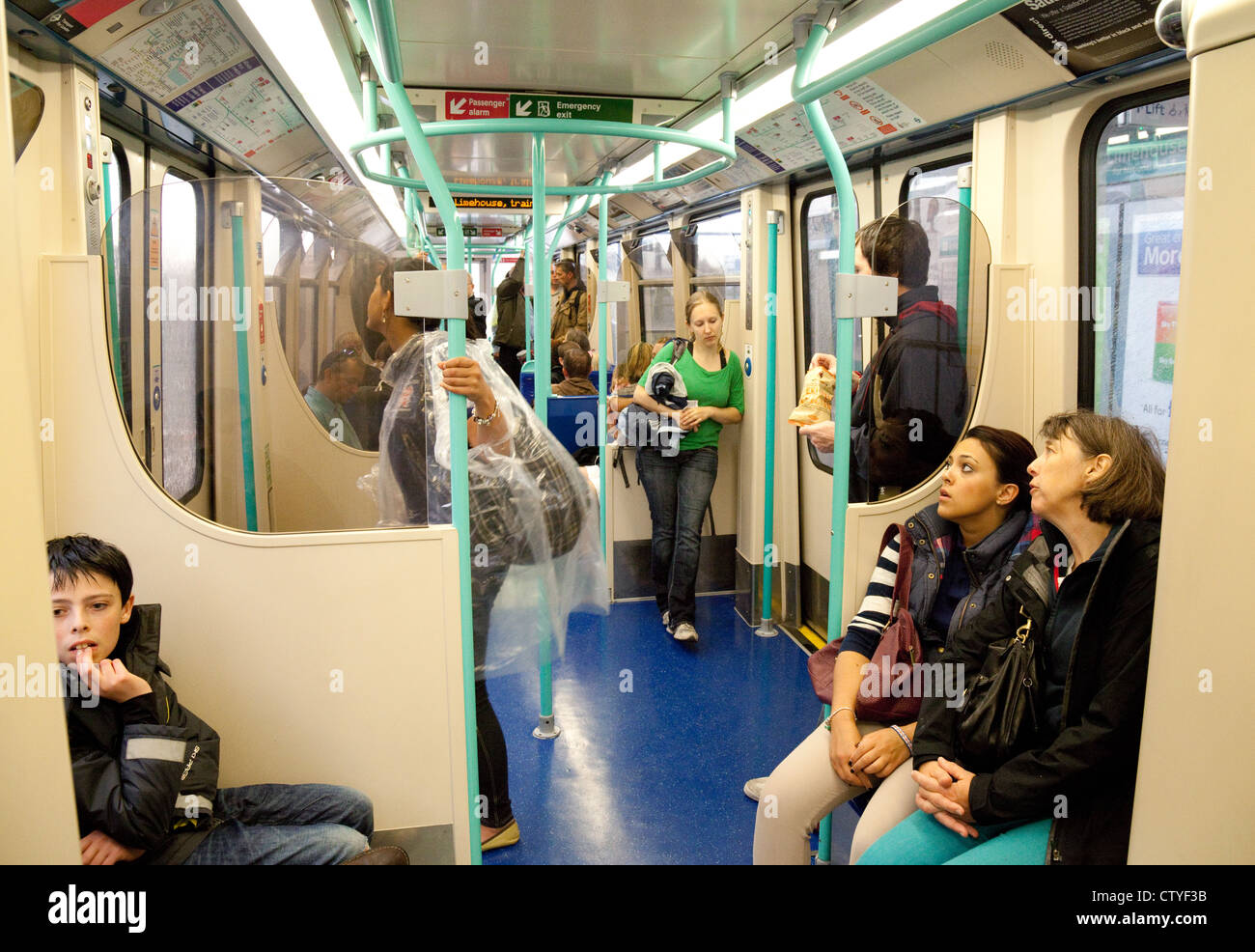 Passengers inside a carriage of a train, London Docklands Light Railway (DLR); London UK - Stock Image
