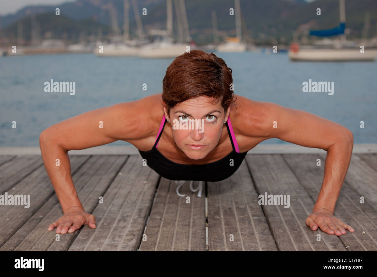 fit healthy middle age woman doing press ups. - Stock Image