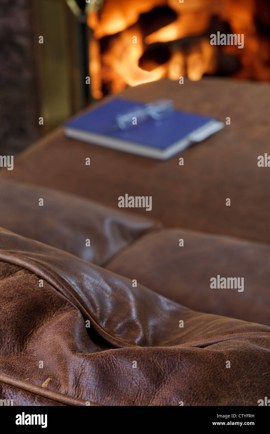 Comfortable leather sofa to read by the fire - Stock Image